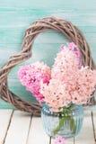 Jacintos rosados frescos en florero y corazón decorativo en la madera blanca Imagenes de archivo