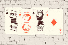 Jack, βασίλισσα, βασιλιάς και άσσος Τυποποιημένες κάρτες παιχνιδιού στο ύφος grunge στο υπόβαθρο τουβλότοιχος επίσης corel σύρετε Στοκ Φωτογραφίες