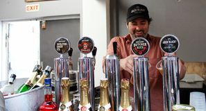 Jack Black Barman. A smiling bartender pours pints of beer and lager at a market stand in Cape Town, South Africa royalty free stock photography
