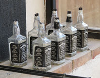 Jack Daniel`s bottles used as candle holders in Kaunas Stock Images
