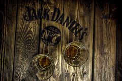 Jack Daniel`s sign on a rustic wooden pallet table with whiskey glasses stock photography