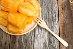 Jack fruit in wooden plate  on old wood background. Fresh jack fruit on wooden plate with fork. On old wood background Royalty Free Stock Image