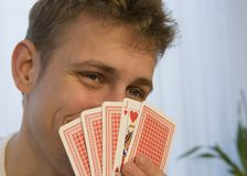 Jack of hearts. Young man shyly flirting behind a hand of poker cards displaying a jack of hearts royalty free stock photos