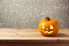 Jack lantern pumpkin on wooden table over bokeh background. Halloween holiday. Celebration Stock Images