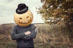 Jack-Laterne mit einer Axt und einem Kürbis auf seinem Kopf in einem Hutdouble Stockbild