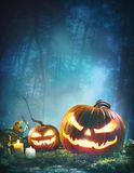 Jack o' lanterns glowing at moonlight in front of spooky fores stock photo