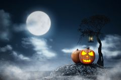 Jack-o-lantern above the rock with lantern hanging on the branch stock photos