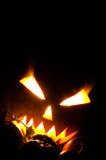 Jack-o-lantern with blazing eyes. Big Jack-o-lantern with blazing eyes on black background and small pumpkins Stock Photos