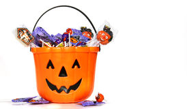 Jack-o-Lantern bucket filled with candies on white Royalty Free Stock Images
