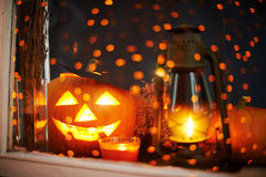 Jack-o-lantern. With burning candles near by in a window royalty free stock photos