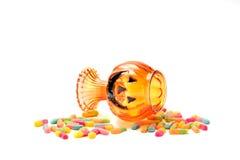 Jack-o-lantern glass jar with  candy. Jack-o-lantern candy glass jar with a pile of colorful Halloween candy Stock Photos