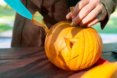 Jack o' Lantern. Close up of man's hand cutting with knife a pumpkin as he prepares a jack-o-lantern Royalty Free Stock Photo