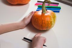 Jack-o-lantern DIY. the boy draws a face on the pumpkin. Preparing for the Halloween party Stock Photography