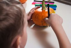 Jack-o-lantern DIY. the boy draws a face on the pumpkin. Preparing for the Halloween party Stock Image
