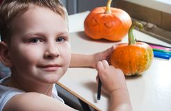 Jack-o-lantern DIY. the boy draws a face on the pumpkin. Preparing for the Halloween party Royalty Free Stock Images