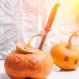 Jack-o-lantern DIY. to carve a pumpkin with a knife. The two pumpkins on the background of the foil. Halloween background Stock Photo