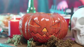 Jack-o-lantern halloween decor element on a table at a halloween party. Candles and skull decoration stock video