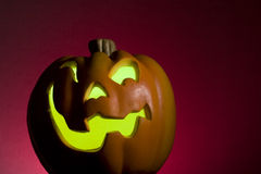 Jack O Lantern Horizontal. Jack O Lantern with a green glow and red background Royalty Free Stock Images
