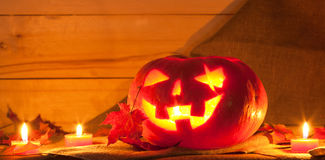 Jack O' Lantern. And maple leaves on the table. Pumpkin carved for Halloween Stock Photo