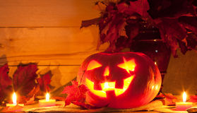 Jack O' Lantern. And maple leaves on the table. Pumpkin carved for Halloween Stock Photos