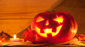 Jack O' Lantern. And maple leaves on the table. Pumpkin carved for Halloween Stock Image
