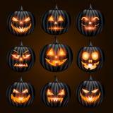 Jack o lantern pumpkin faces glowing on black background Royalty Free Stock Image