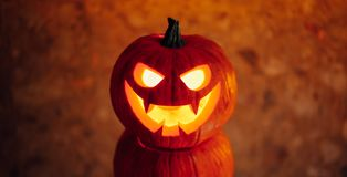 Jack-o-lantern pumpkin orange light, Halloween background. Close-up view stock photography