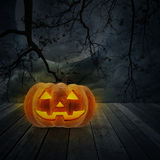 Jack O Lantern pumpkin on wood floor over dead tree, moon and cl Royalty Free Stock Photography