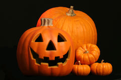 Jack o lantern with pumpkins. Seasonal harvest of squash and a Halloween face carved in a jack o lantern Royalty Free Stock Photos