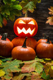Jack o lantern on pumpkins pile with leaves Royalty Free Stock Photos
