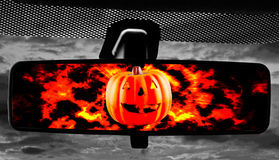 Jack-o-Lantern in rearviewmirror. Jack-O-Lantern on fire reflected in rearviewmirror of a car Stock Photo