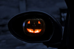 Jack-o-Lantern in rearviewmirror. Jack-o'-Lantern seen in rearviewmirror of a car Royalty Free Stock Photography