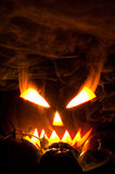Jack-o-lantern in smoke. Jack-o-lantern with blazing and smoky eyes in smoke and small pumpkins Royalty Free Stock Photography