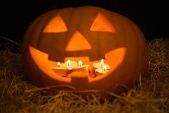 Jack-O-lanterna da abóbora de Dia das Bruxas iluminada com velas sobre b imagem de stock royalty free