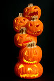 Jack O Lanterns. Halloween decoration - a stack of pumpkins carved into lighted jack-o-lanterns on black background stock image