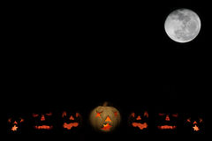 Jack o-lanterns and full moon with space for text. Lit jack o-lanterns under a full moon against a black night sky with room for your text Royalty Free Stock Photography