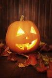 Jack o lanterns  Halloween pumpkin face on wooden background Royalty Free Stock Photo