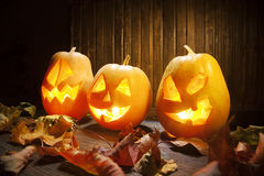 Jack o lanterns Halloween pumpkin face on wooden background Royalty Free Stock Photo