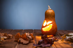 Jack o lanterns Halloween pumpkin face on wooden background Royalty Free Stock Images