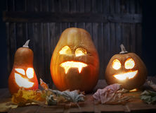 Jack o lanterns Halloween pumpkin face on wooden background Royalty Free Stock Image