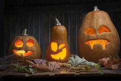 Jack o lanterns Halloween pumpkin face on wooden background Stock Photography
