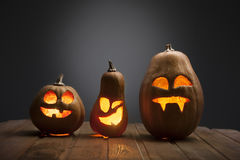 Jack o lanterns Halloween pumpkin face on wooden background Stock Photos