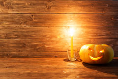 Jack o lanterns Halloween pumpkin face on wooden background. Royalty Free Stock Image