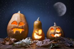 Jack o lanterns Halloween pumpkin face on wooden background. And autumn leafs royalty free stock images