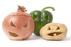 Jack-o-Lanterns made out of Fruit and vegetables. Halloween faces carved into vegetables such as onion, potato and capsicum instead of pumpkin forming special Stock Photography