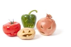 Jack-o-Lanterns made out of Fruit and vegetables. Halloween faces carved into vegetables such as potato, tomato, onion and capsicum instead of pumpkin forming Royalty Free Stock Photo