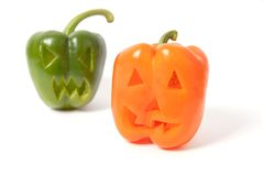 Jack-o-Lanterns made out of vegetables. Halloween faces carved into orange and green capsicum vegetables instead of pumpkin forming special jack o lanterns Royalty Free Stock Image