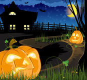 Jack o Lanterns on the path. Leading to the house with glowing windows Royalty Free Stock Images