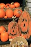 Jack-O-Lanterns and several pumpkins on green shelving Royalty Free Stock Photos