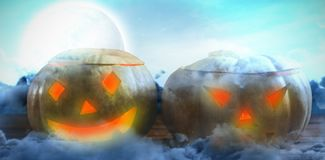 Composite image of jack o lanterns on wooden table. Jack o lanterns on wooden table against view of sea against sky Stock Photo